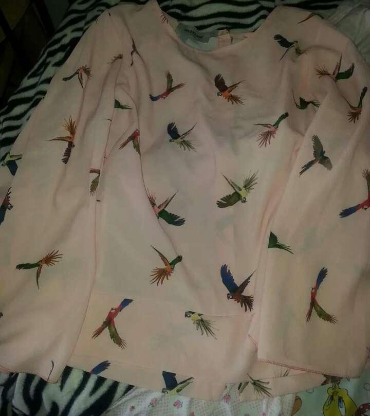 Imagen camiseta dorada sin manga con etiqueta brusa rosa de pájaros de colores talla S