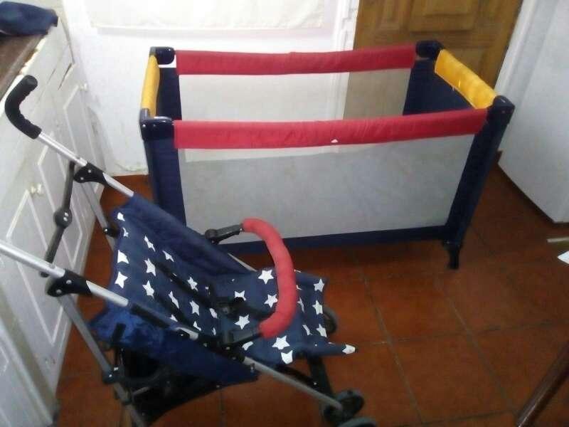 Imagen carrito de niño/a junto a un parque cuna plegable con su funda