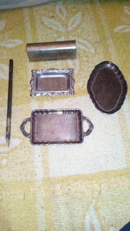Imagen bandejitas de plata una cajita una pluma antigua y algo de bisuteria.