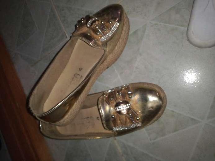 Imagen zapatos dorados con moño de lenjuelas